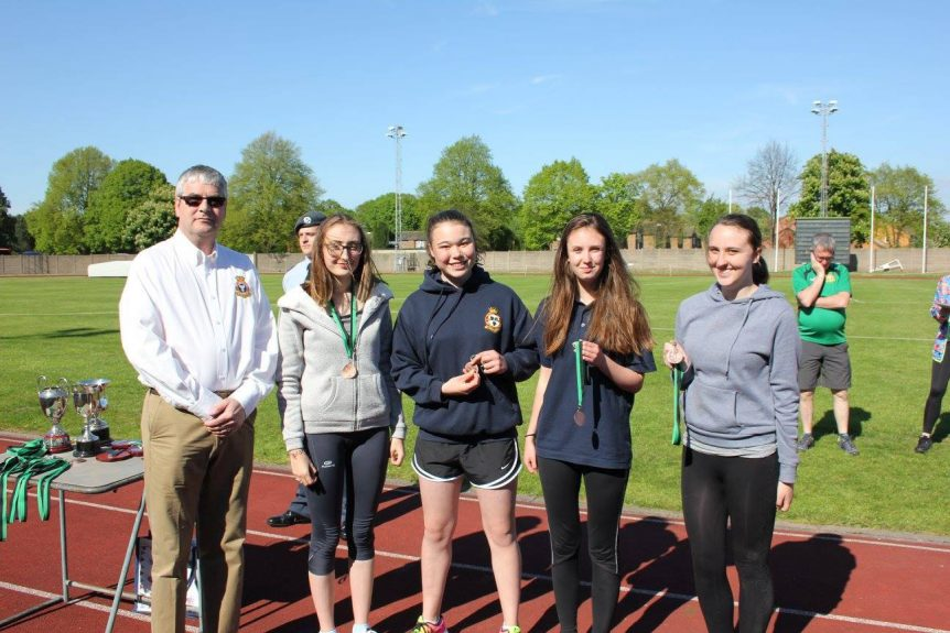Cadet Corporal A. Cooper, Cadet Flight Sergeant C. Weetman, Cadet Corporal C. Walthorne and Cadet Corporal J. Tucker collecting their medals from Wing Commander Andy Griffin Officer Commanding West Mercian Wing for coming 3rd in the relay for their age category during the athletics event.