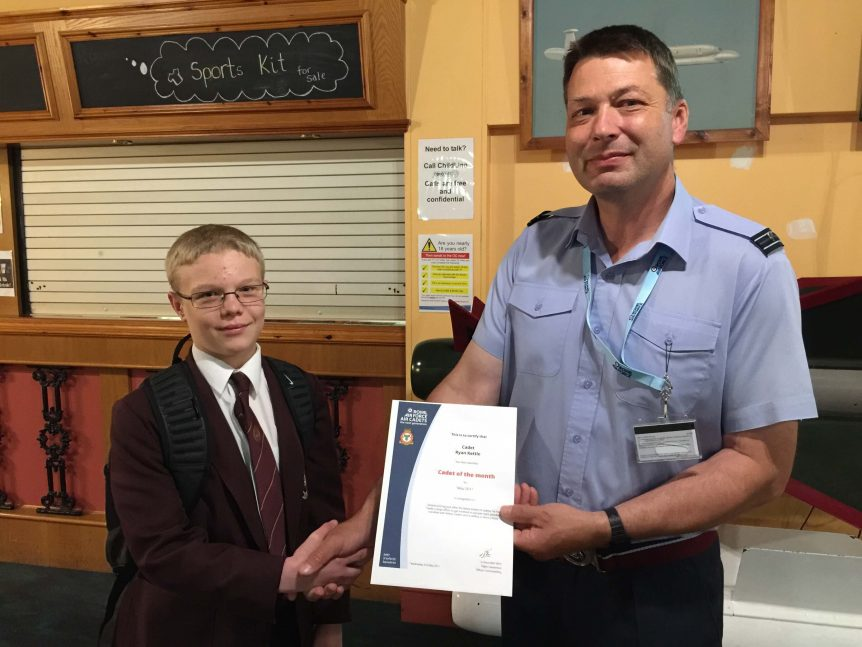 Cadet R. Kettle collecting his 'Cadet of the month' certificate from Flight Lieutenant Giles Vince RAFVR(T)